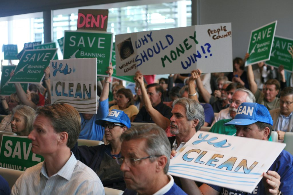 Banning Ranch project protesters and supporters wave signs during the California Coastal Commission meeting Wednesday. — Photo by Sara Hall ©
