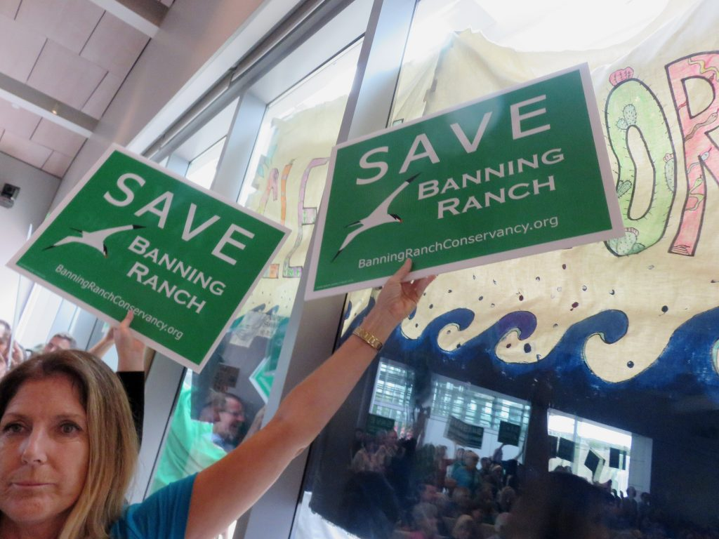 "An opponent to the project holds a ""Save Banning Ranch"" sign in front of an NBR supporter's ""Clean. Restore. Open."" banner, while the audience is reflected in the glass, during the California Coastal Commission meeting Wednesday. — Photo by Sara Hall ©"