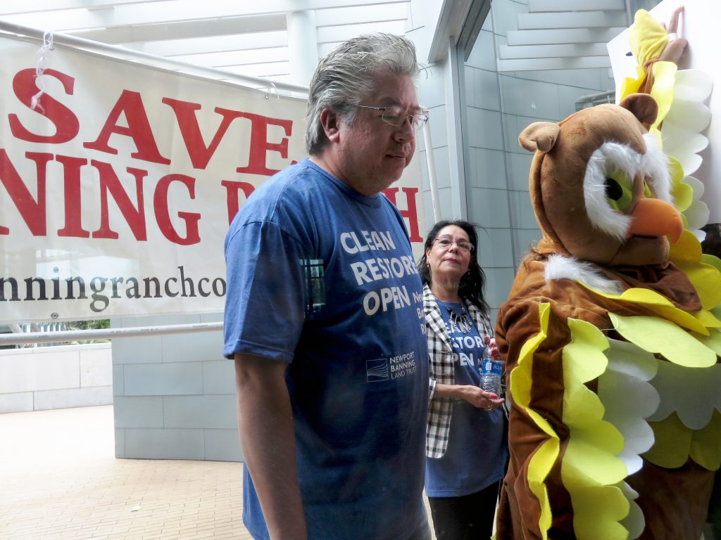 A NBR supporter and an opponent dressed as an owl watch the Coastal Commission meeting from outside the window. — Photo by Sara Hall ©