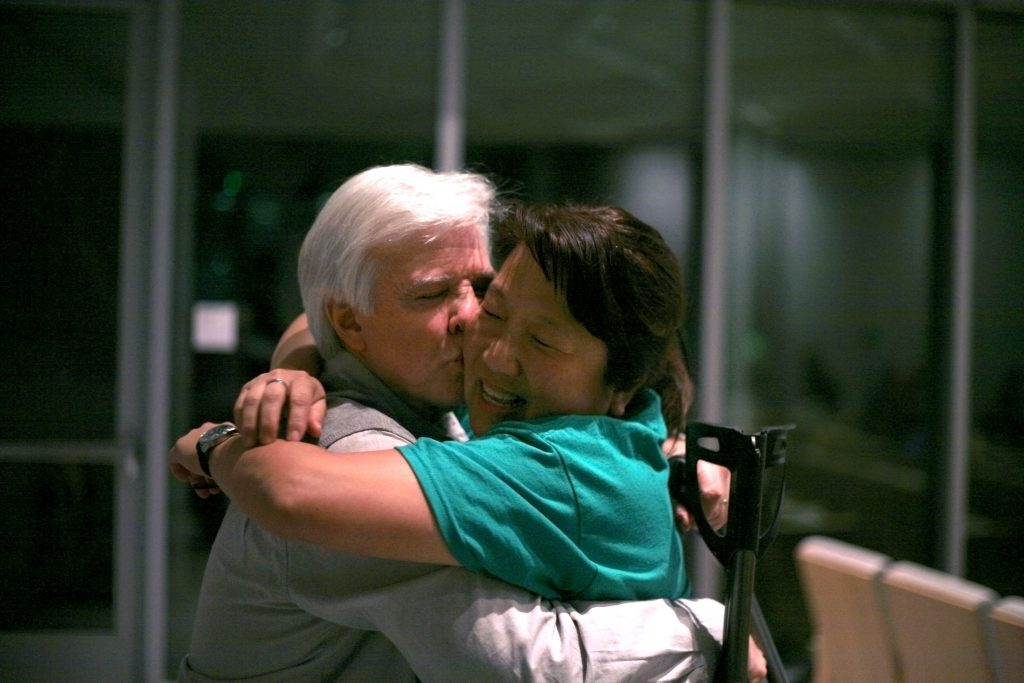 Banning Ranch Conservancy executive director Steve Ray hugs and kisses his wife, Shan, in celebration after the Coastal Commission voted to deny the proposed development. — Photo by Sara Hall ©