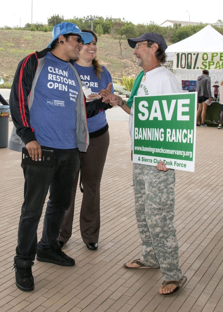 Banning Ranch supporters Guillermo Durado and Vanessa Roque talk with opponent Johnny Hawk outside the CCC meeting on Wednesday. — Photo by Charles Weinberg ©