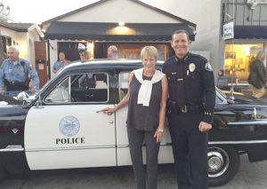 Balboa Island Museum and Historical Society President Shirley Pepys and Newport Beach Police Chief Jon Lewis pose in front of a classic Ford police cruiser.