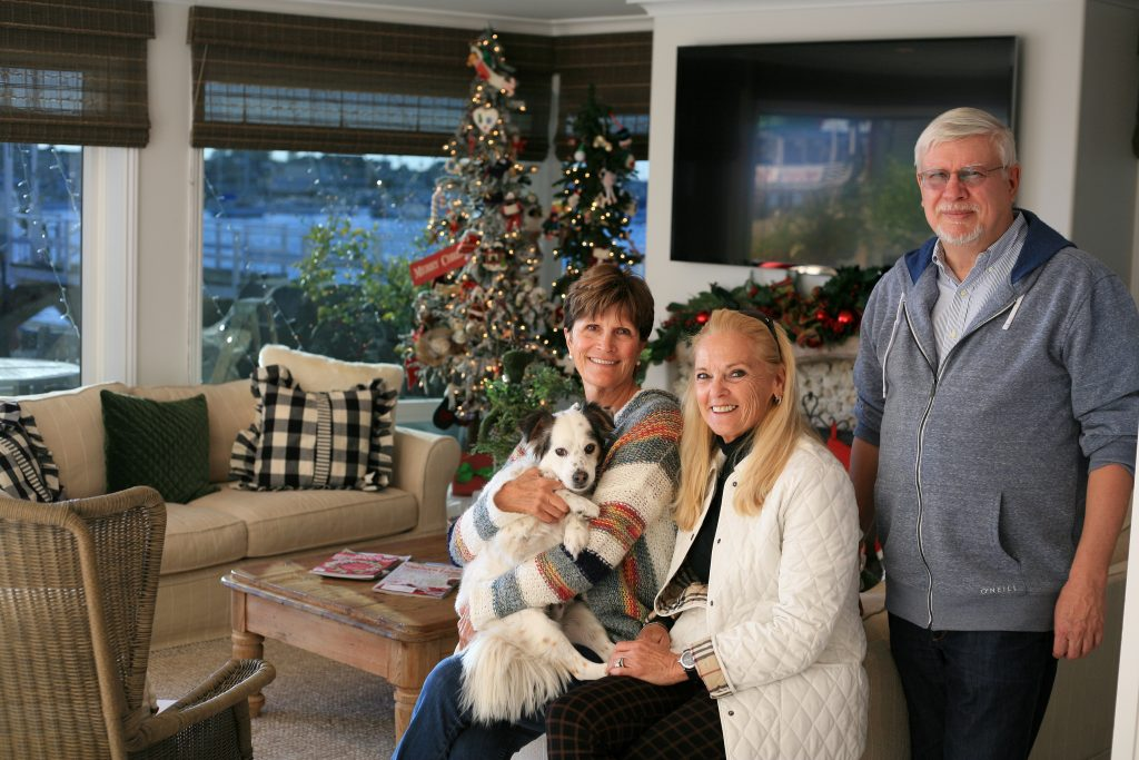 (left to right) 20th Annual Balboa Island Holiday Home Walking Tour homeowner participant Diana Conners (holding her dog, Dewey), tour docent and Balboa Island Improvement Association board member Kristine Taft, and tour chair and BIIA board member Tom Popplewell, pose for a photo in Conner's living room. — Photo by Sara Hall ©