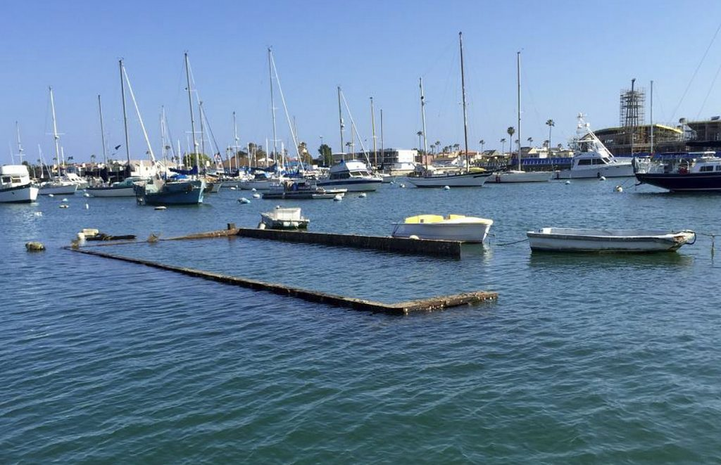 The top portion of the sunken Shellmaker, Inc., scow, Gemini, is still visible in Newport Harbor during low tide. — Photo courtesy the city of Newport Beach ©