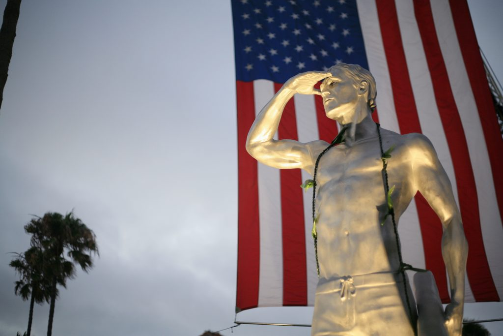 An American flag hangs behind a statue depicting Ben Carlson, the first Newport Beach lifeguard to die in the line of duty, that was unveiled July 6 . — Photo by Sara Hall ©