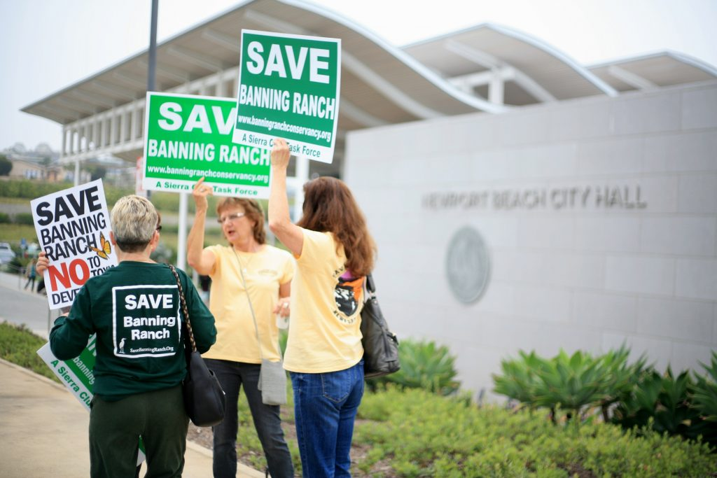 Opponents of the Banning Ranch project wave signs outside the Newport Beach Civic Center on Thursday morning. The California Coastal Commission met in NB council chambers and was scheduled to vote on the controversial project on May 12, but it was postponed. — Photo by Sara Hall ©