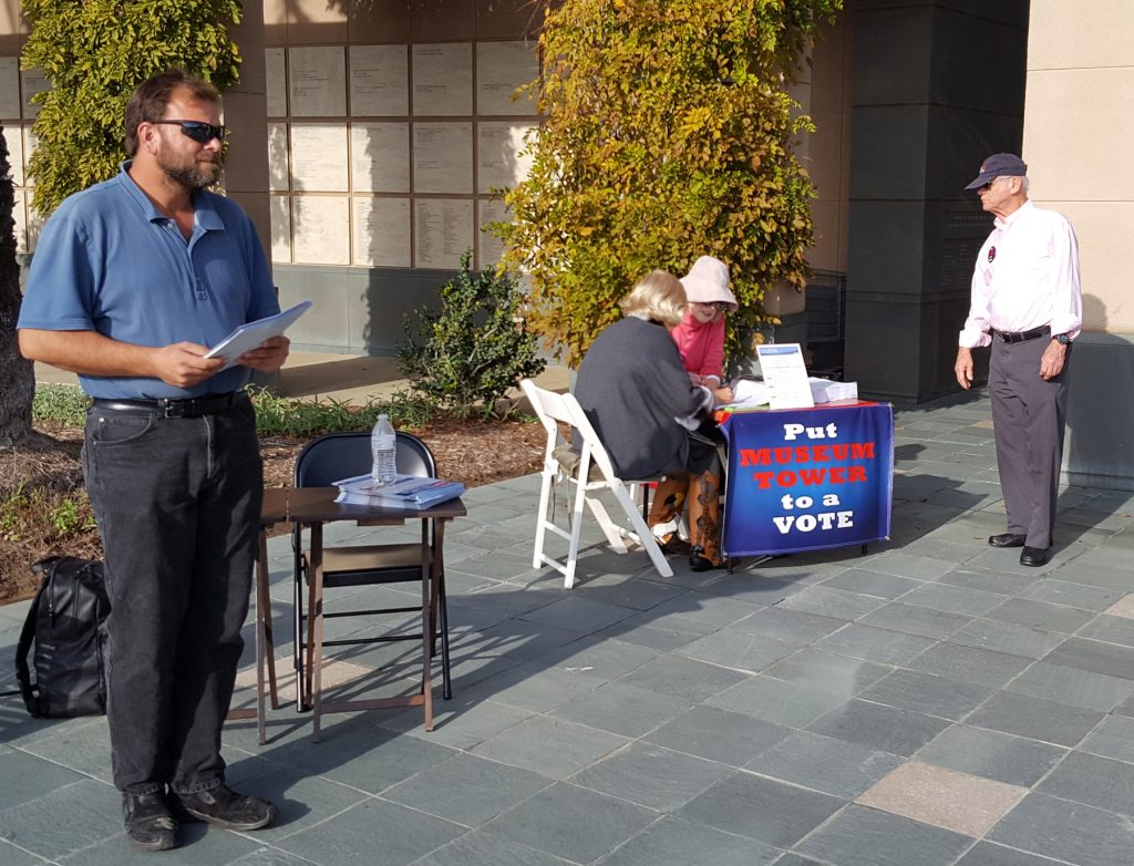 "A representative of OCMA Urban Housing, LLC (left) passes out ""Petition Hurts Our Kids"" flyer near the Line in the Sand petition table in front of the Newport Beach Public Library"