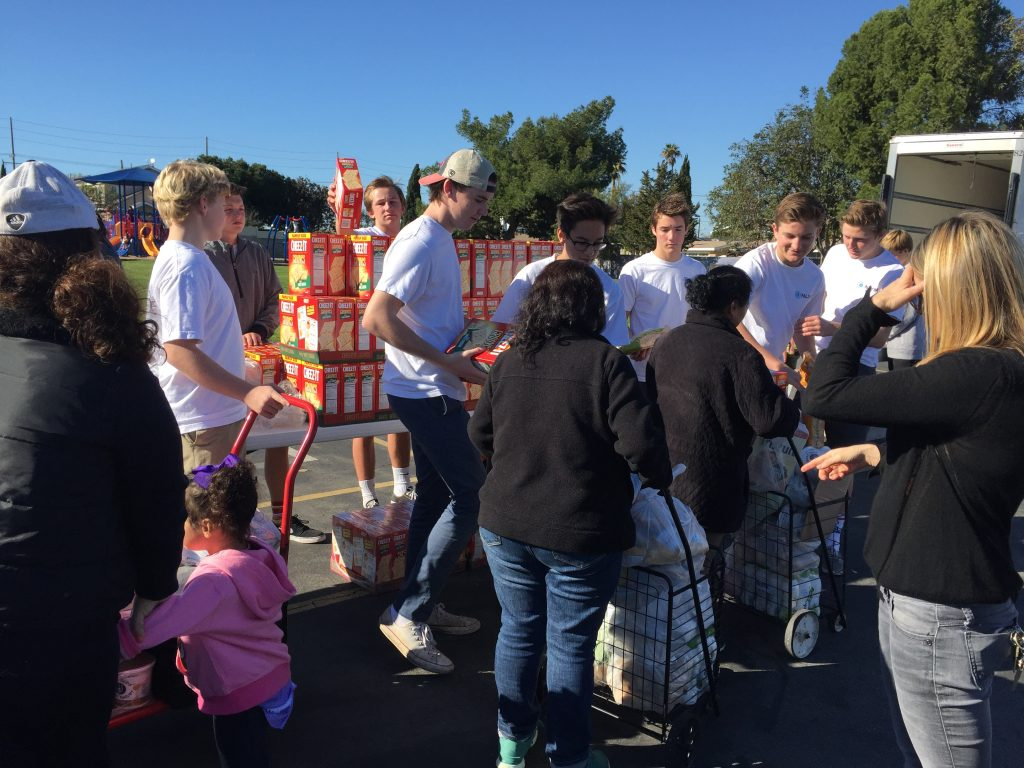 Members of the Newport-Mesa chapter of the National League of Young Men hand out food to people in need at an event on Saturday.  — Photo courtesy of NLYM ©