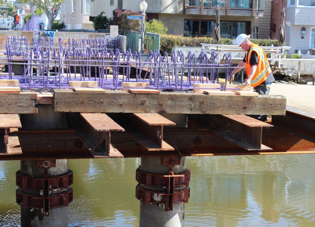 A worker measures reinforcement bars atop falsework on Park Avenue Bridge on Balboa Island — Photo by Victoria Kertz ©