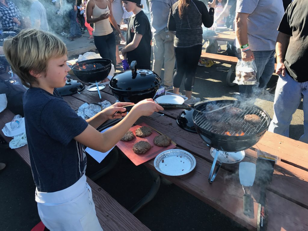 Young grill master Peter Kertz flips a burger in the kid's competition