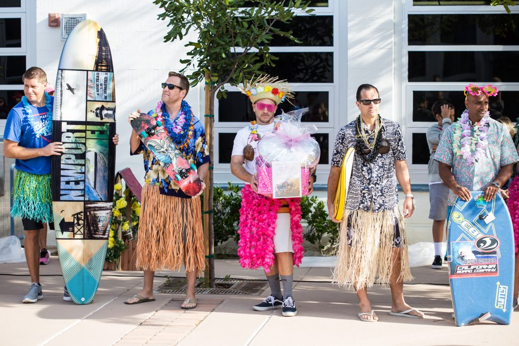 The Hula for Moola fundraising event kicked off March 10 at the Newport Elementary School morning flag deck with a group of Newport El dads dressed up as hula dancers and performing in front of about 500 students. — Photo courtesy Dena Baron , co-chair of Newport El School Foundation ©