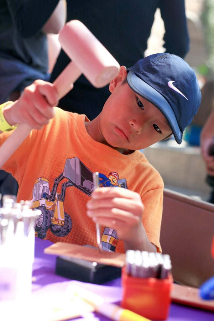 Peyton Lau, 7, of Irvine hammers in a stamp into a leather bracelet at a craft booth at the fair. — Photo by Sara Hall ©