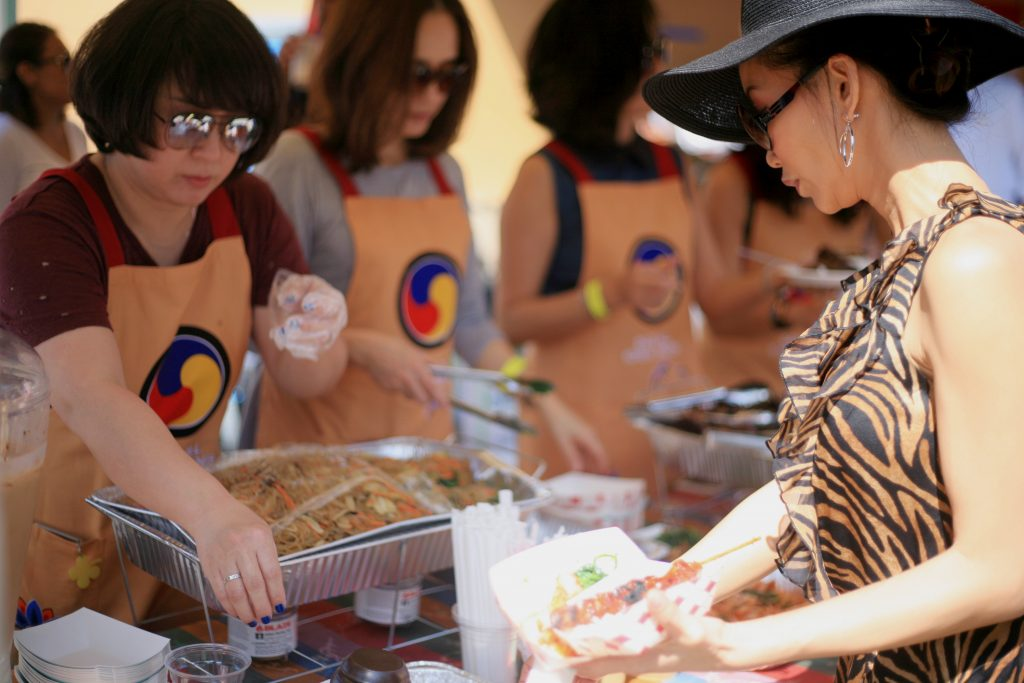 Sage parent Bee Walbridge picks out some food from the Korean food booth on Saturday. — Photo by Sara Hall ©