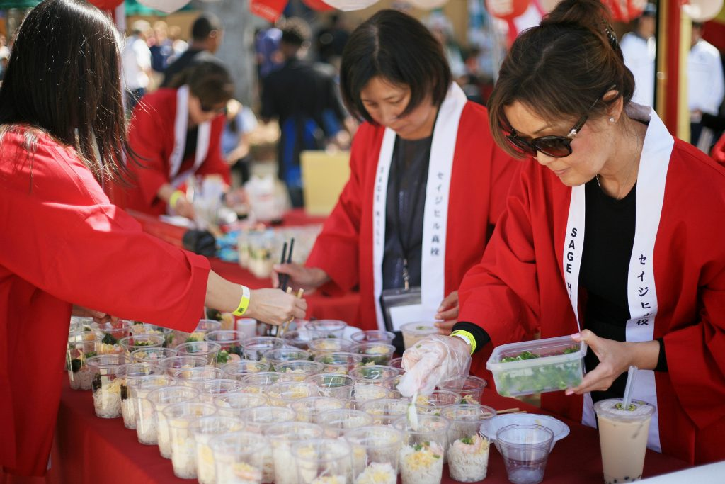 Sage parents (left to right) Junko Hara, Emi Nishinaka and Reiko Stauss fill cups with chilled somen noodles for the Japan food booth.  — Photo by Sara Hall ©