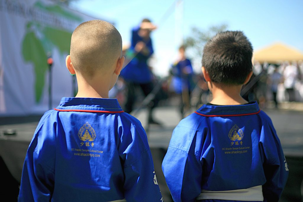 Two of the younger members of Kung Fu Master Shi Yanqing from the Orange County Shaolin Temple Cultural Center in Costa Mesa watch as their fellow Kung Fu trainees perform on stage.  — Photo by Sara Hall ©