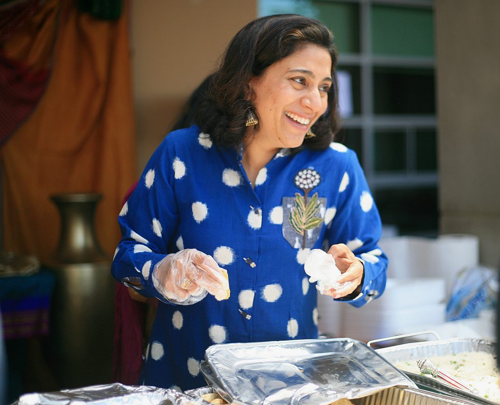 Sage parent Renu Chokshi laughs as she helps guests at the Indi food booth at the Multicultural Fair on Saturday. — Photo by Sara Hall ©