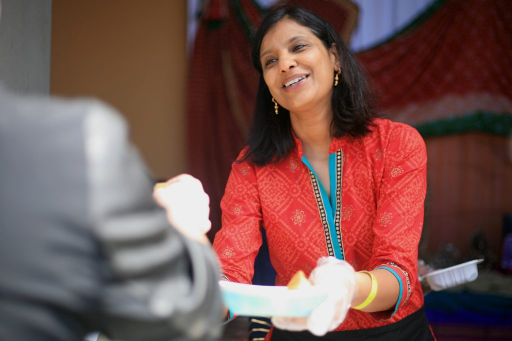 Shilpa Kamdar, mom of a Sage Hill student, smiles and hands a guest food from the India booth on Saturday. — Photo by Sara Hall ©