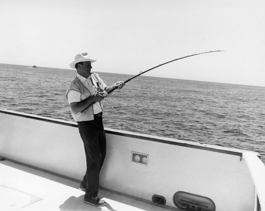 John Wayne fishing off the side of his boat, the Wild Goose. He loved to sail and often visited Catalina Island. — Photo courtesy John Wayne Enterprises ©