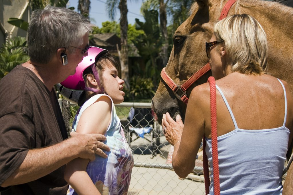Michelle Hoops gets close to her favorite horse, Peanut, with the assistance of her dad, Mike, at Back Bay Therapeutic Riding Club (BBTRC) in Newport Beach before hand-feeding him a carrot. Horse manager Vickie Tombrello stands with Peanut as he gently takes the treat from Michelle's hand. — Photo by Sara Hall ©