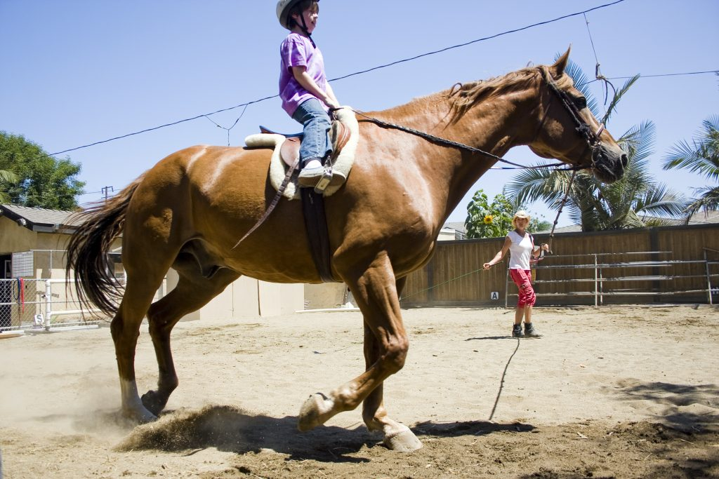 Bernadette Olsen holds a lead and helps Connor McCrury, 8, trot Scruffy around the dusty backyard arena at Back Bay Therapeutic Riding Club. Connor's mother said his confidence has increased dramatically since he began the program in May. — Photo by Sara Hall ©