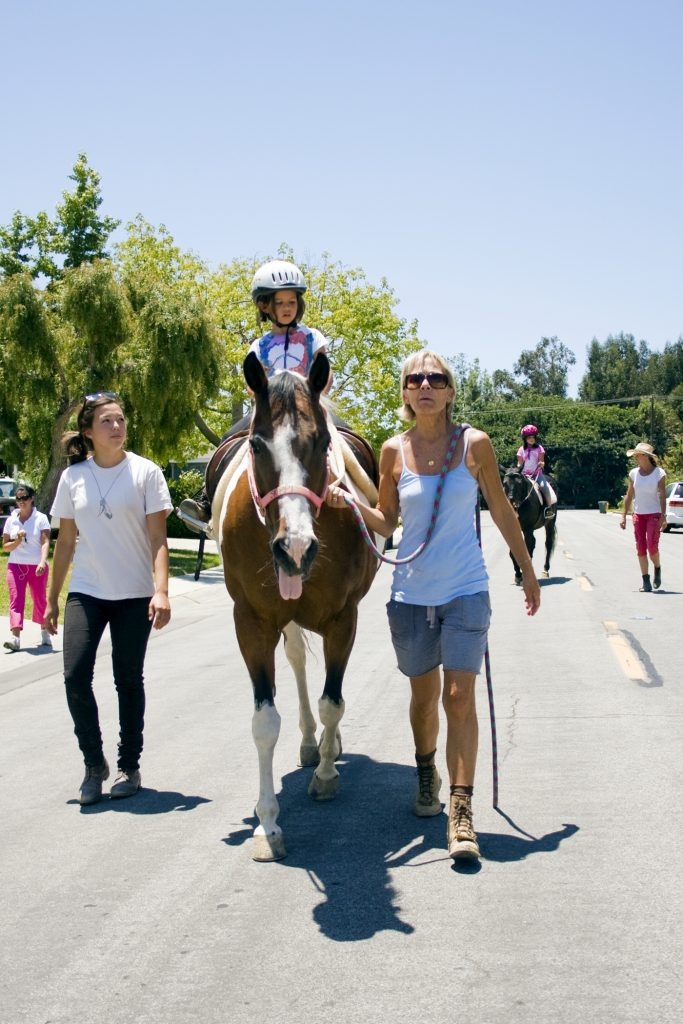Back Bay Therapeutic Riding Club (BBTRC) student sisters Katie, 7, (front) and Karoline Shannon, 9, ride horses during their weekly session. The group that walks with them in support, from left to right, is their mother, Katherine, volunteer Katharina Chiu, horse manager Vickie Tombrello, and BBTRC founder Bernadette Olsen. — Photo by Sara Hall ©