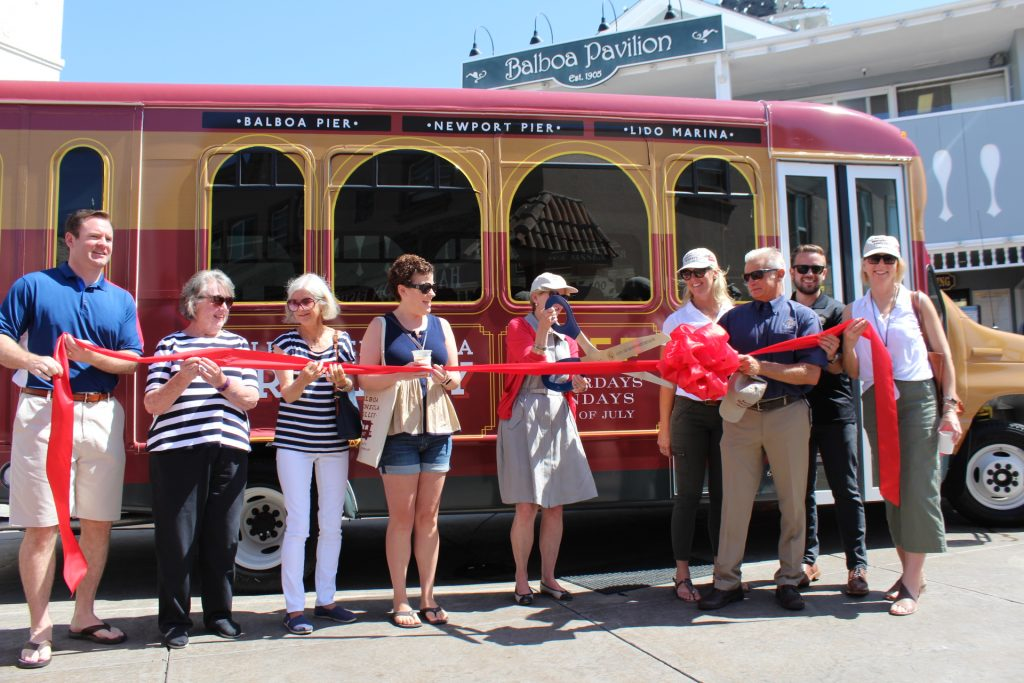 Councilmember Diane Dixon (center) cuts the ribbon marking the launch of the Balboa Peninsula Trolley