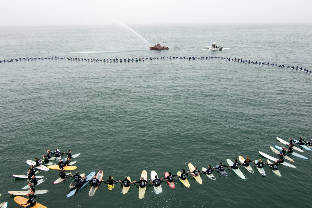Surfers hold hands to form a circle as they break a world record and the Orange County Sheriff's Harbor Patrol boat sprays water into the air in the background. — Photo by Jim Collins ©