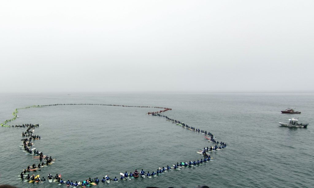 A total of 511 surfers hold hands and form a circle in Huntington Beach on Tuesday, breaking a Guinness World Record for largest surfing paddle out. — Photo by Jim Collins ©