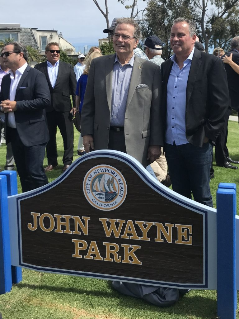 Patrick (left) and Ethan Wayne, sons of late actor John Wayne, pose for photos by the new sign for John Wayne Park. — Photo by Victoria Kertz ©