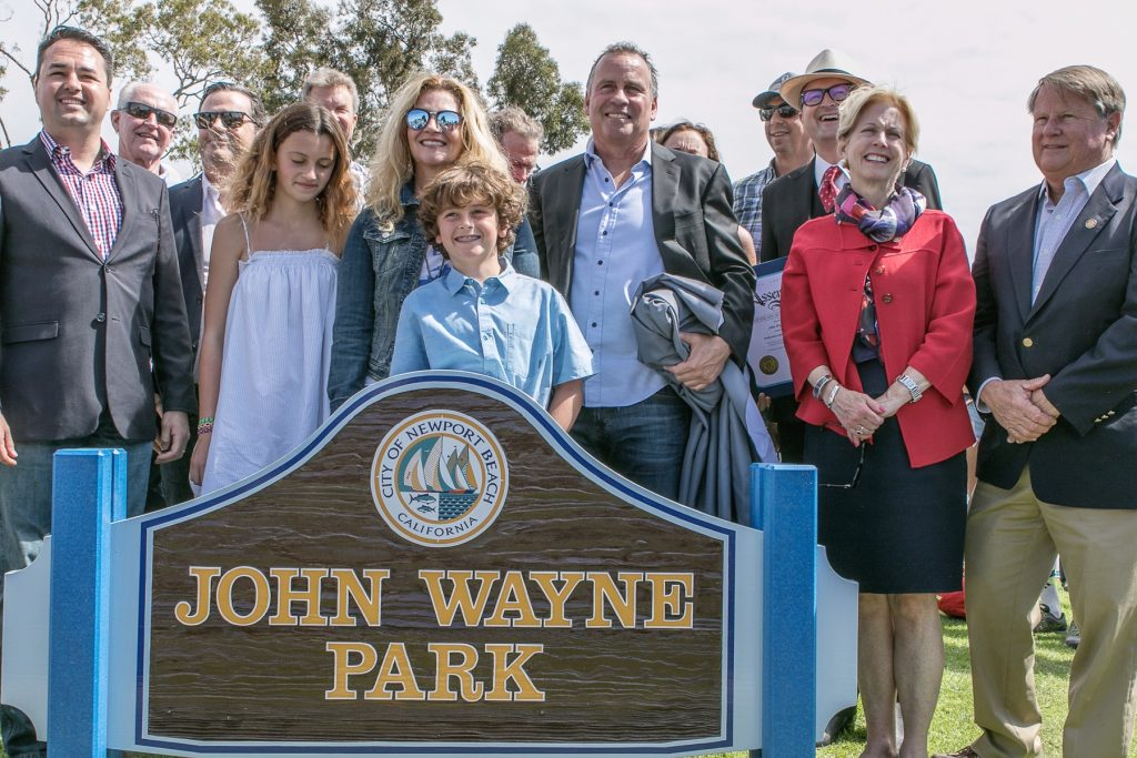 Family members of Newport Beach's famous former resident, John Wayne, pose for photos with city and regional officials by the sign for the park recently named after the actor. — Photo by VJim Collins ©